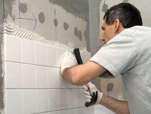 Construction worker tiling bathroom wall