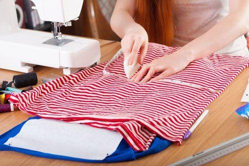due mani con un vestito a righe bianche e rosse su un tavolo e accanto una macchina da cucire