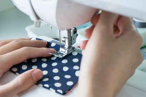 due mani con una macchina da cucire mentre cuce una stoffa a blu a pois bianchi
