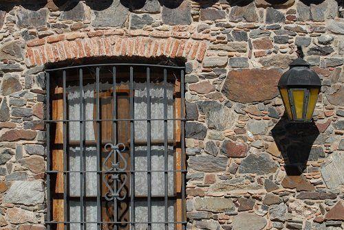 Griglia di ferro in una finestra di legno in una parete di pietra e un farol di ferro nella parete