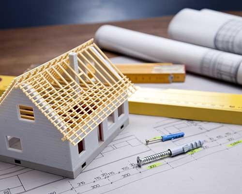 Delle viti e dei tasselli,un disegno di un progetto e una casa in miniatura