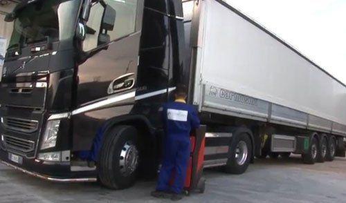 Un meccanico visto dal dietro con una tuta blu con un carrello con un macchinario rosso e accanto un camion nero con un rimorchio bianco
