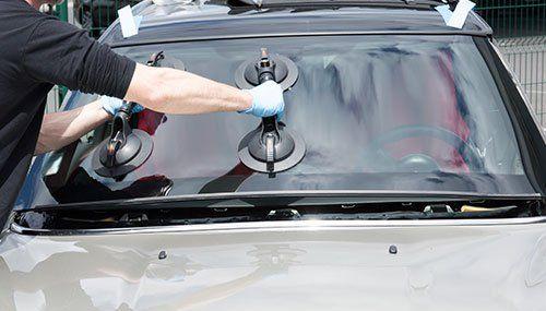 Due braccia di un meccanico che impugnano due supporti con delle ventose appoggiate su un vetro di una vettura
