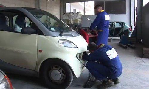 Un meccanico con una tuta blu chinato a terra mentre ripara la parte anteriore di una macchina bianca