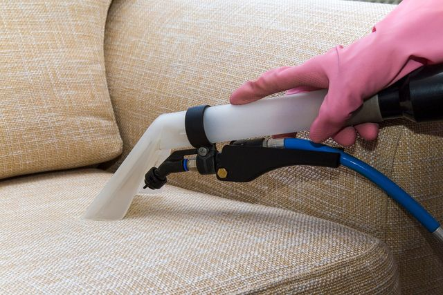 operatore con guanto che aspira la polvere da un divano con un compressore