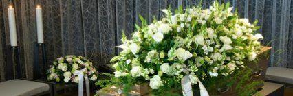 cuscinetto di fiori bianchi su bara