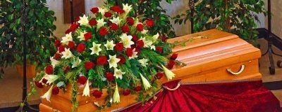 cuscinetto di fiori rossi e bianchi su bara