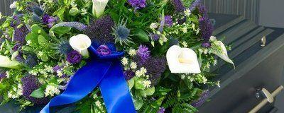 cuscinetto di fiori bianchi e viola su bara