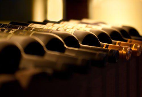 Bottiglie di vino rosso su una mensola di legno