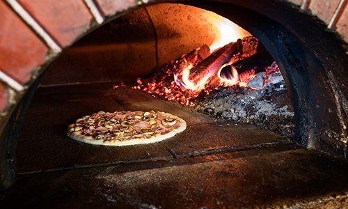 una pizza farcita in un forno a legna