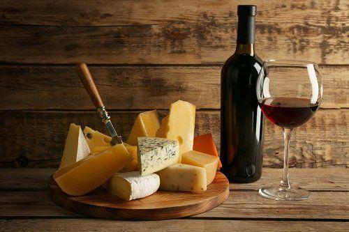 un tagliere di formaggi,una bottiglia e un bicchiere di vino rosso