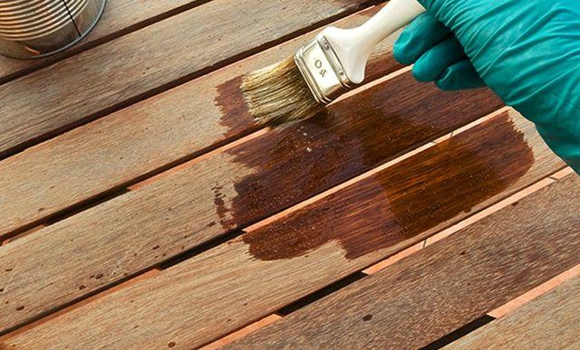 Una mano applica dello smalto su delle assi di legno