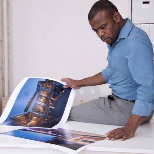 A man looking at some colour printed sheets
