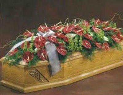 una bara in legno con dei fiori rossi