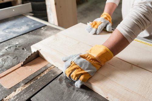 due mani con dei guanti che tengono un asse di legno