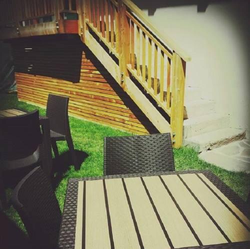 Estera del ristorante dove il legno dei mobili si combina con il verde dei giardino e il sole che li illumina