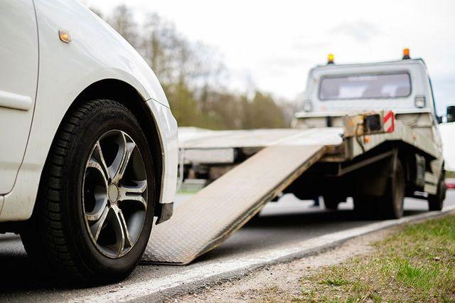 Loading broken car on a tow truck by the roadside in West Salem