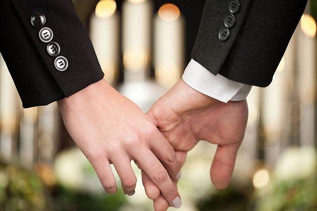 Coppia al funerale che si tiene la mano per consolarsi a vicenda