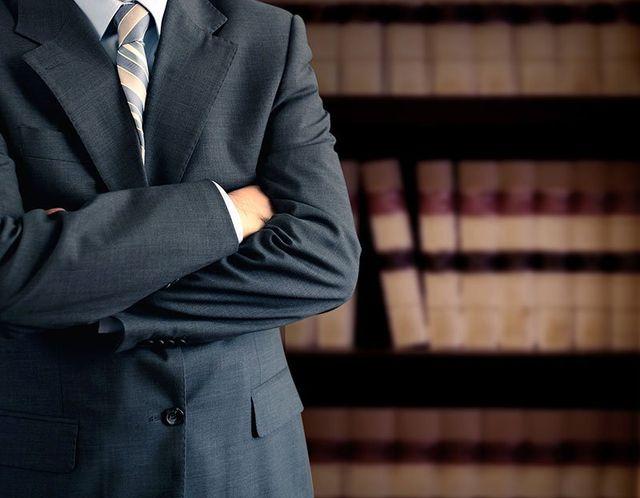 Uomo a braccia conserte mostrando serietà con una biblioteca legale dietro