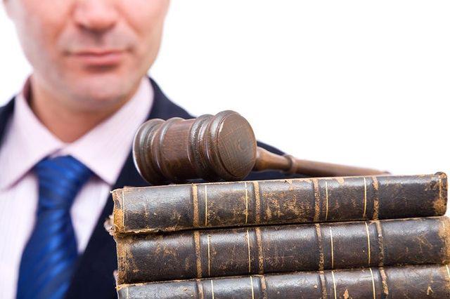 Vecchi libri di leggi con un martello di giustizia sopra e un uomo dietro