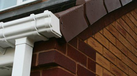 neat, white guttering and square section downpipe
