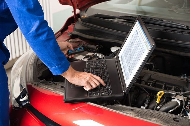 Mechanic examining car engine in La Crosse