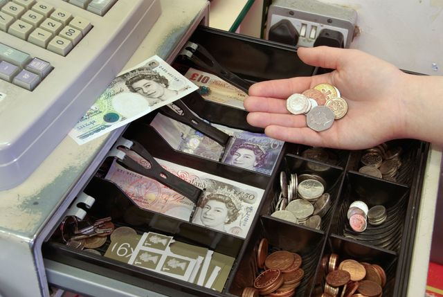 An open till drawer containing coins, bank notes and stamps
