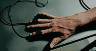 Polygraph wires attached to a man's hand