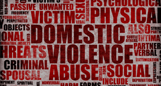 Red poster with capital letter red words such as PASSIVE, CRIMINAL, DOMESTIC, VIOLENCE, ABUSE - all the things this company tackles