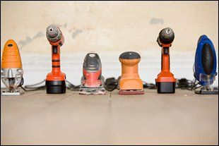 Six handheld power tools including drill and sander
