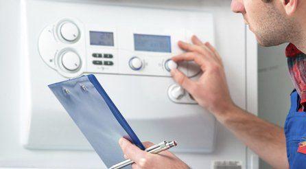 A gas safe technician checking a boiler