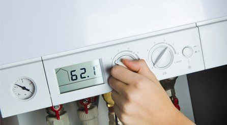 A boiler thermostat being turned