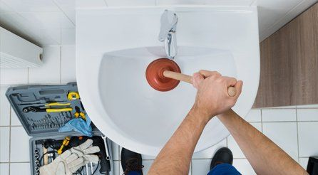 A plumber using a plunger on a bathroom sink