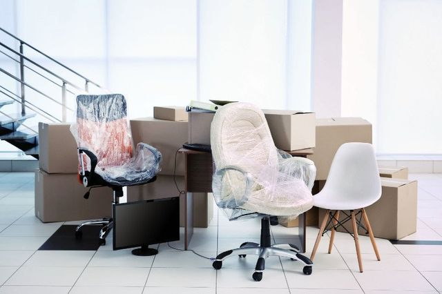 delle sedie da ufficio con della plastica,degli scatoloni,un monitor e una sedia bianca