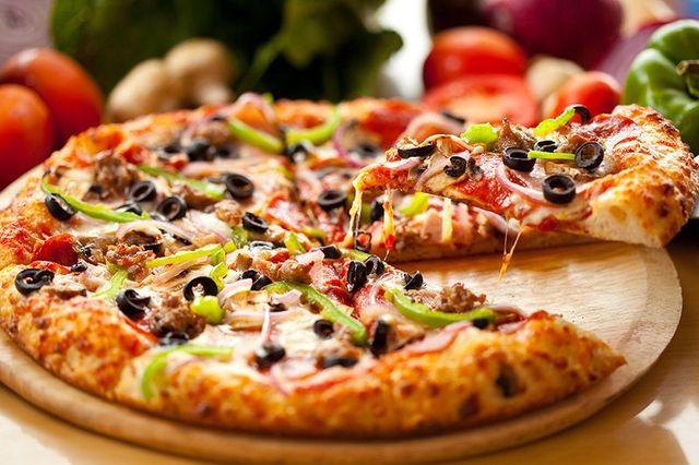 pizza con mozzarella, pomodoro, olive nere, peperoni e salsiccia su un tagliere di legno a Siracusa