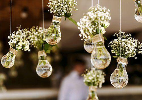 dei vasi di vetro appesi con dei fiori