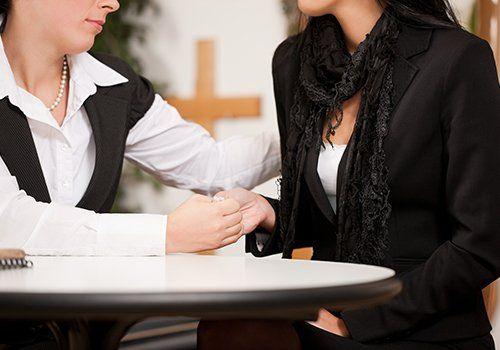 due donne sedute al tavolo vestiti in nero che tengono le mani