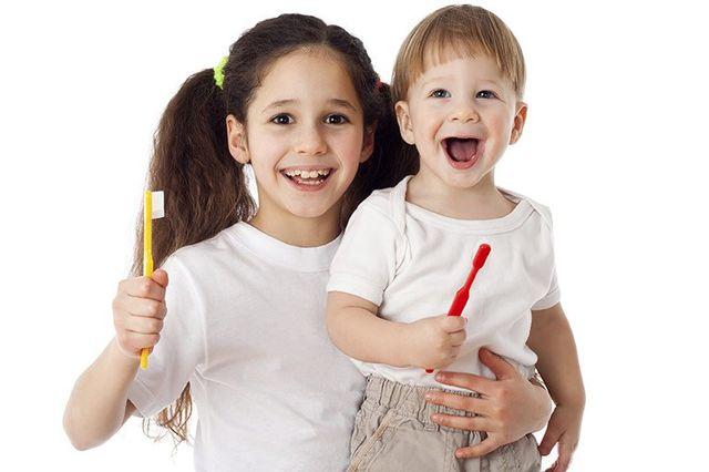 children smiling while brushing teeth