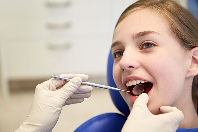 child at dentist getting teeth check up