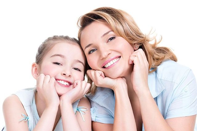 smiling mother and daughter with clean teeth