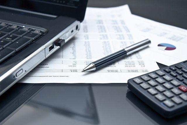 calcoli con fogli di carta laptop e calcolatrice