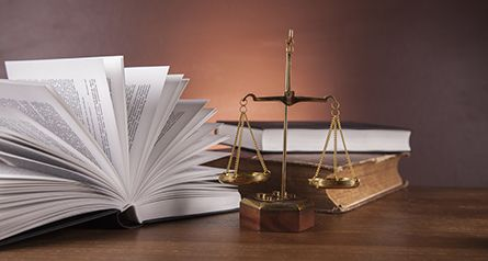 Justice balance scale and law books in our law firm in High Point, NC