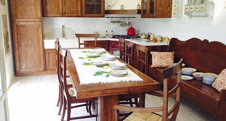 a rustic kitchen complete with table, chairs and a bench
