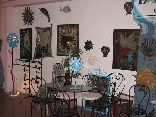 un tavolino in vetro,sedie in ferro battuto e dei quadri