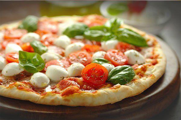 una pizza margherita con delle mozzarelle e del basilico