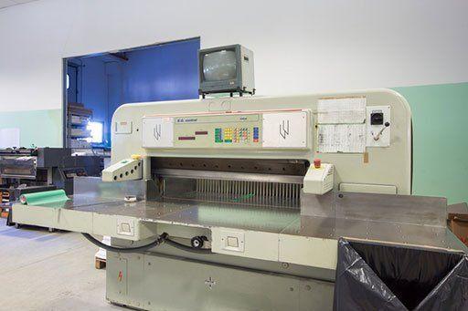 una macchina da stampa e sopra un piccolo monitor grigio spento