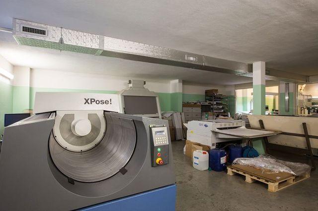 vista di un macchinario da tipografia e sulla destra una macchina da stampa, un bancale di legno dei prodotti chimici