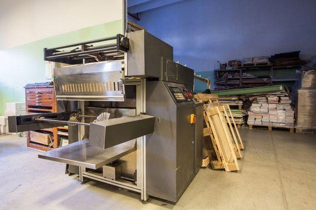 un macchinario industriale di metallo e dietro in lontananza dei bancali con della carta