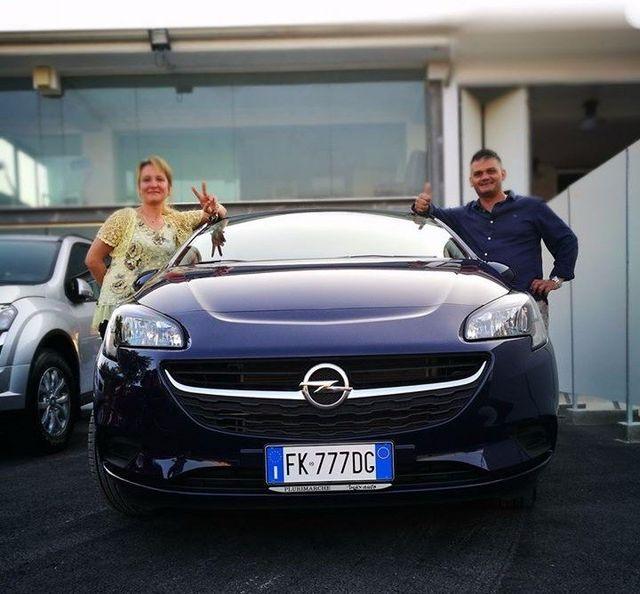 Coppia che sorride felice con un'auto nuova