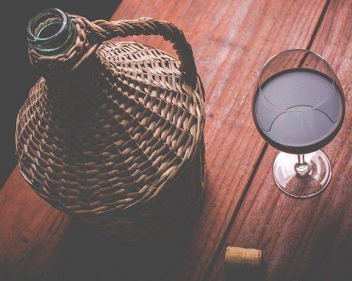 una damigiana e un bicchiere di vino rosso